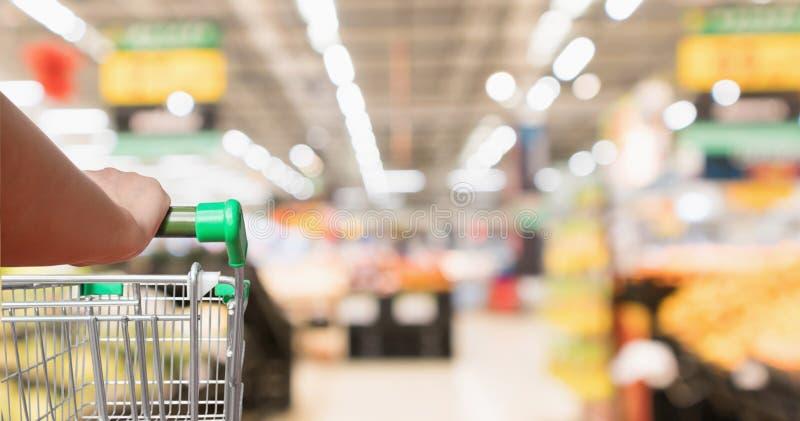 Carro de la compra del supermercado del control de la mano de la mujer con el fondo borroso colmado foto de archivo