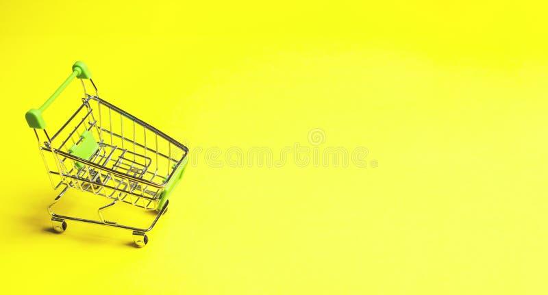 Carro de la compra en fondo amarillo imágenes de archivo libres de regalías