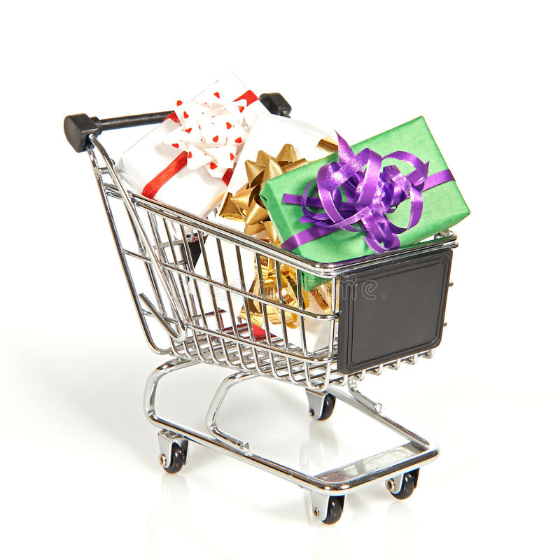 Carro de la compra llenado de los regalos de la Navidad imagen de archivo libre de regalías