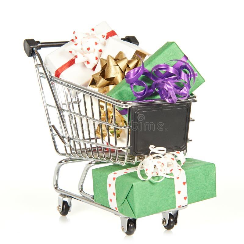 Carro de la compra llenado de los regalos de la Navidad imagen de archivo
