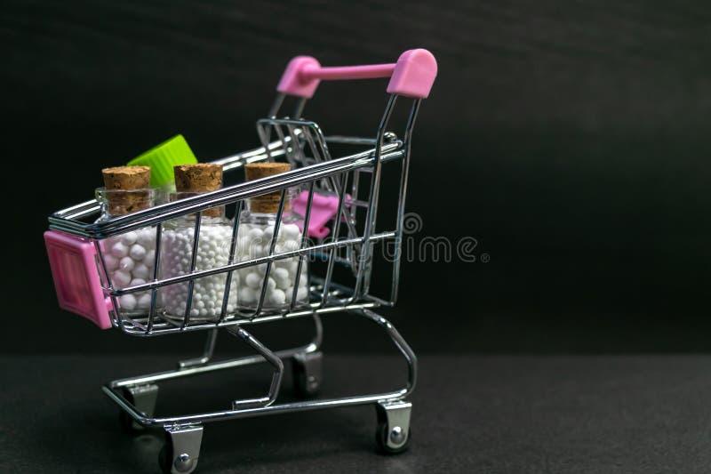 Carro de la compra llenado del vidrio homeopático y de las botellas plásticas de la medicina en fondo oscuro Concepto en línea de fotografía de archivo libre de regalías