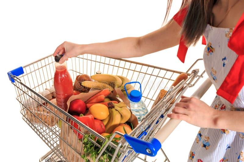 Carro de la compra lleno en la tienda con las verduras frescas y el primer de las manos fotos de archivo libres de regalías