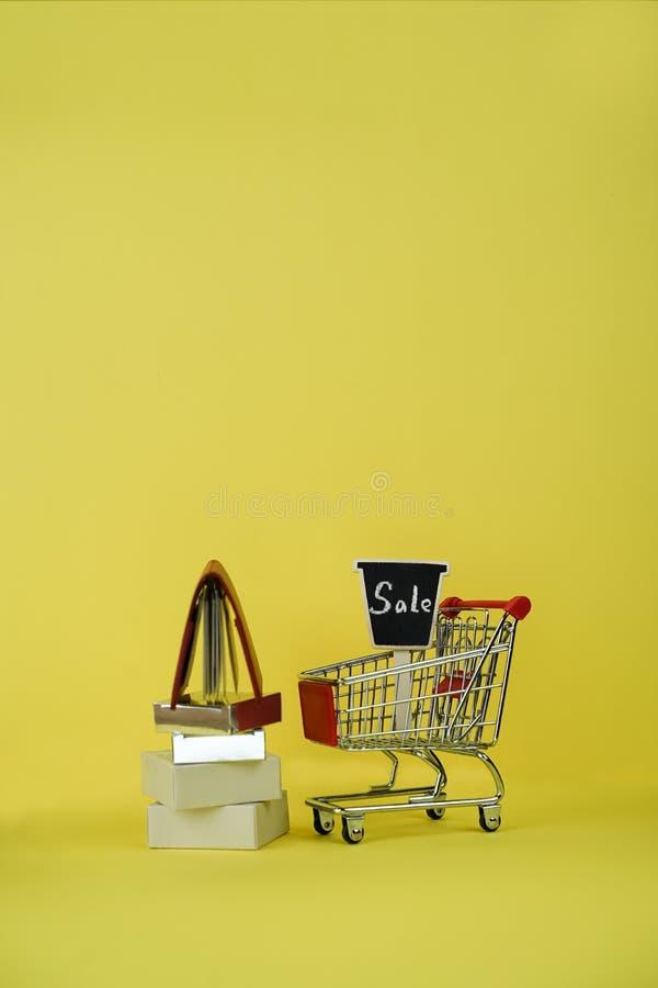 Carro de la compra o carretilla de la tienda del supermercado en el fondo amarillo brillante, concepto creativo, espacio de la co foto de archivo