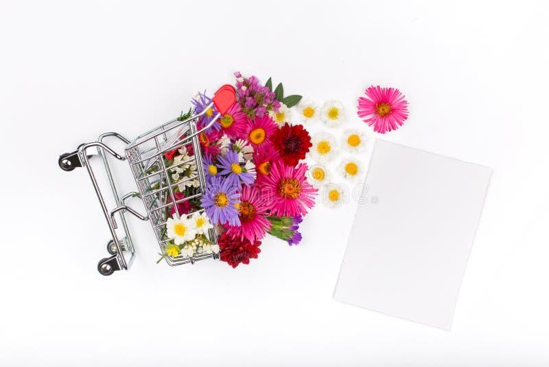 Carro de la compra por completo de diversos wildflowers con la tarjeta en blanco foto de archivo