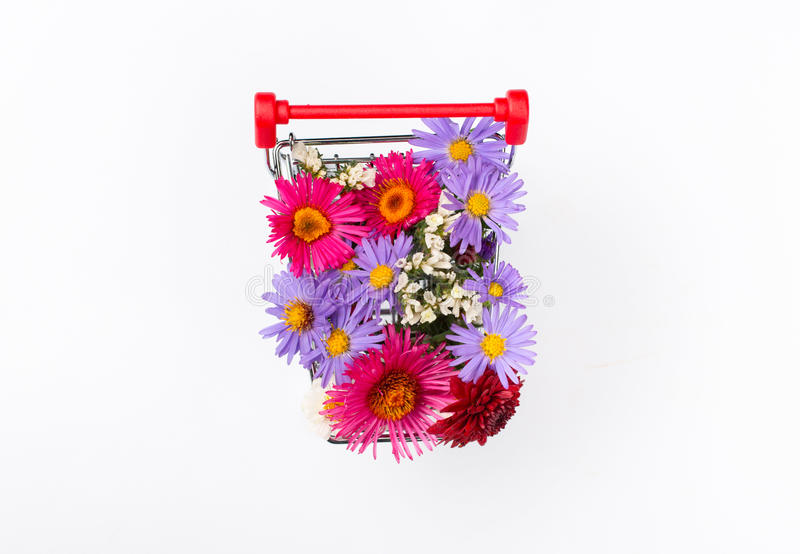 Carro de la compra por completo de diversos wildflowers en el fondo blanco foto de archivo