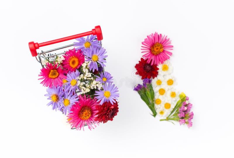 Carro de la compra por completo de diversos wildflowers en el fondo blanco fotos de archivo