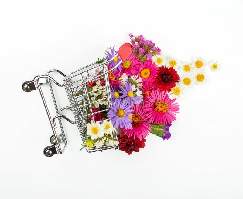 Carro de la compra por completo de diversos wildflowers en el fondo blanco imágenes de archivo libres de regalías