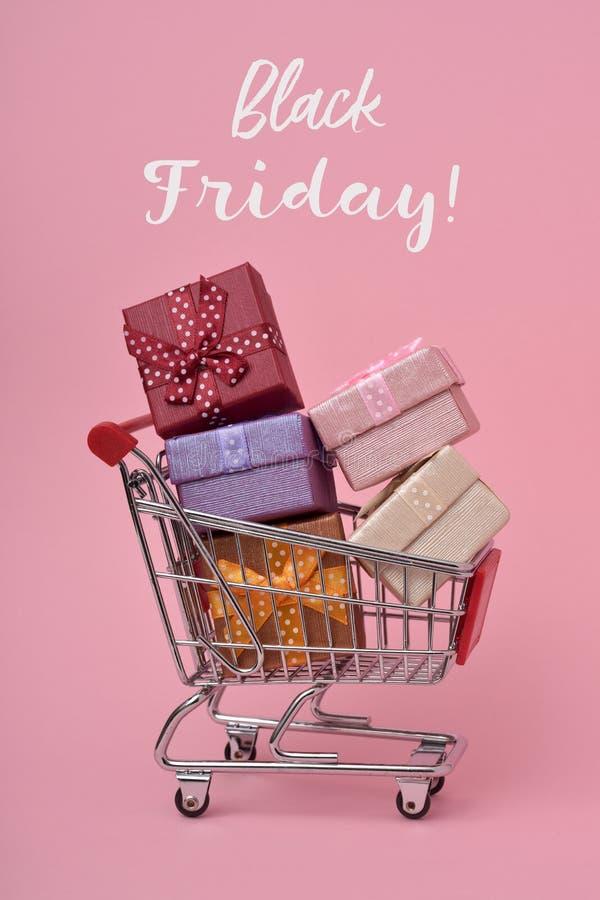 Carro de la compra por completo de los regalos y del texto viernes negro fotografía de archivo