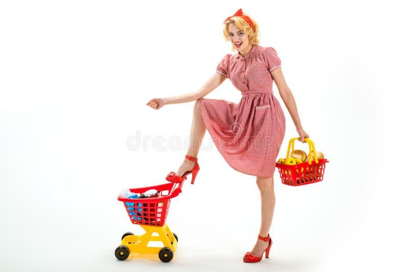 Carro de la compra que monta Servicio a domicilio mujer del ama de casa del vintage aislada en blanco ahorros en mujer retra de l foto de archivo libre de regalías