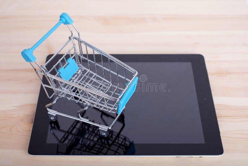 Carro de la compra sobre un Tablet PC en la tabla de madera imagenes de archivo