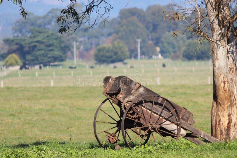 Carro de la granja que aherrumbra contra árbol imagenes de archivo
