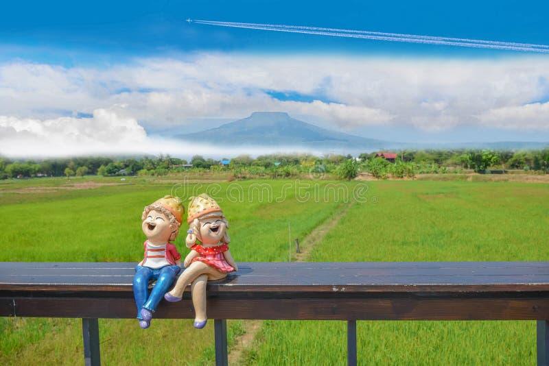 carro de las historietas del muchacho y de la muchacha en asiento de madera con el campo verde del arroz de arroz, la nube hermos imagen de archivo libre de regalías