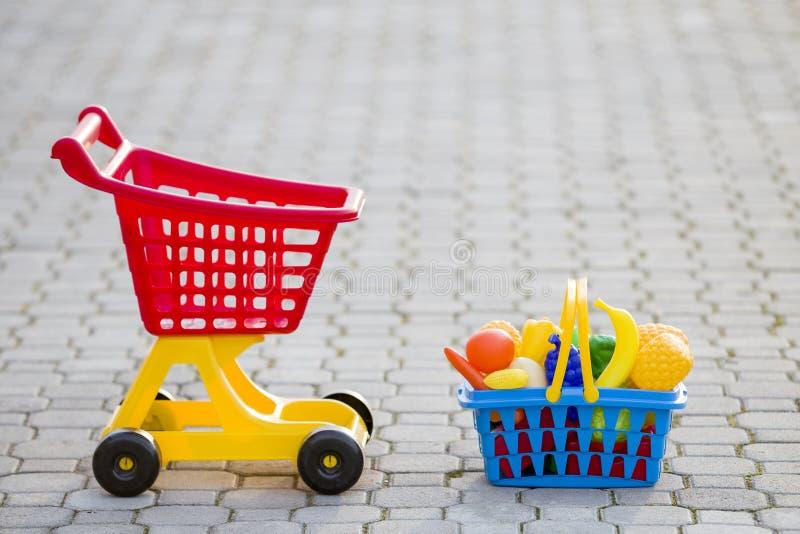 Carro de mão da compra e uma cesta com frutas e legumes do brinquedo Brinquedos coloridos plásticos brilhantes para crianças fora fotografia de stock royalty free