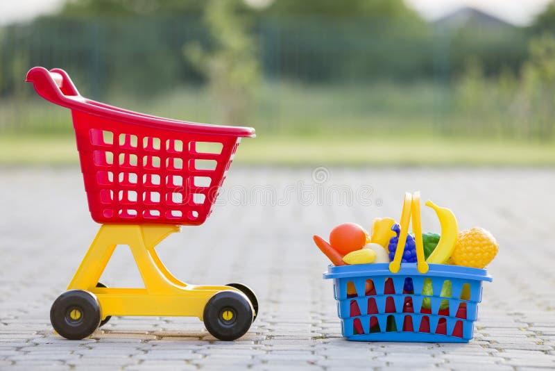 Carro de mão da compra e uma cesta com frutas e legumes do brinquedo Brinquedos coloridos plásticos brilhantes para crianças fora fotografia de stock