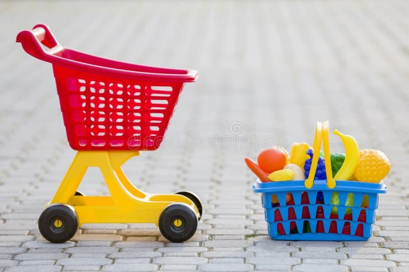 Carro de mão da compra e uma cesta com frutas e legumes do brinquedo Brinquedos coloridos plásticos brilhantes para crianças fora imagem de stock royalty free