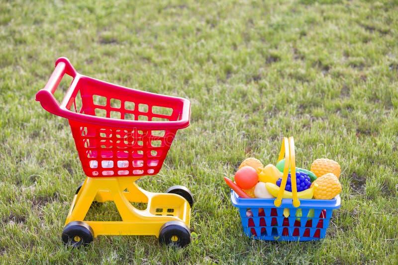 Carro de mão da compra e uma cesta com frutas e legumes do brinquedo Brinquedos coloridos plásticos brilhantes para crianças fora imagem de stock