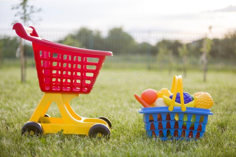 Carro de mão da compra e uma cesta com frutas e legumes do brinquedo Brinquedos coloridos plásticos brilhantes para crianças fora foto de stock royalty free