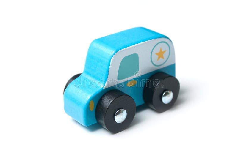 carro de madeira diminuto azul no fundo branco - patrulha da polícia do conceito fotografia de stock royalty free