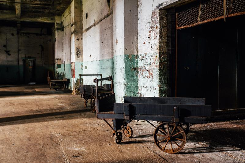 Carro de madera antiguo con las ruedas del arrabio - fábrica de cristal abandonada de la mano fotos de archivo