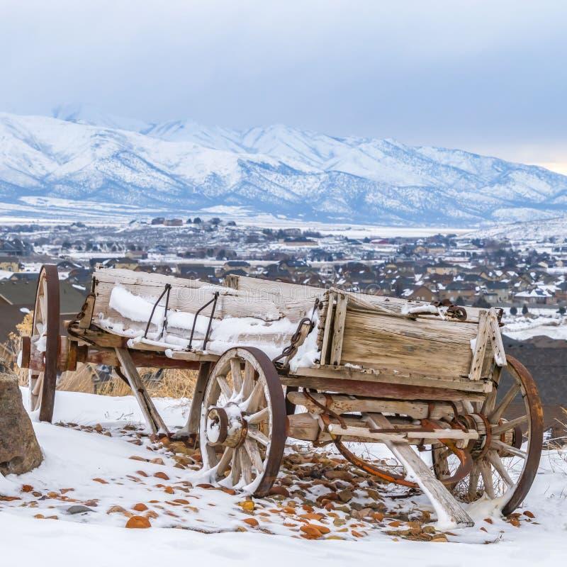 Carro de madera rústico del cuadrado claro al lado de una roca enorme encima de una colina nevosa en invierno imagen de archivo