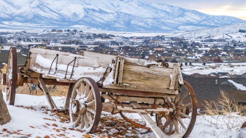 Carro de madera rústico del panorama al lado de una roca enorme encima de una colina nevosa en invierno imagen de archivo libre de regalías