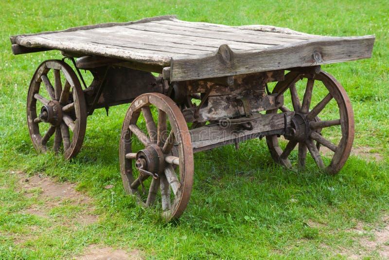 Carro de madera rural viejo vacío en hierba verde del verano fotografía de archivo libre de regalías
