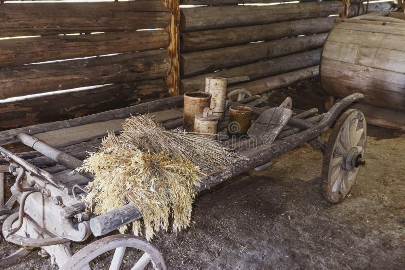 Carro de madera viejo con los oídos secos y los utensilios de madera adentro de una vertiente foto de archivo