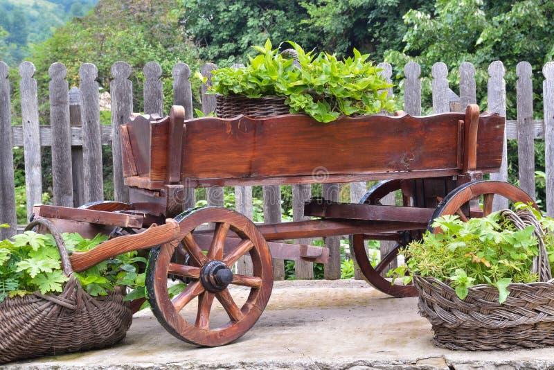 Carro de madera y cestas de mimbre en el patio trasero fotografía de archivo