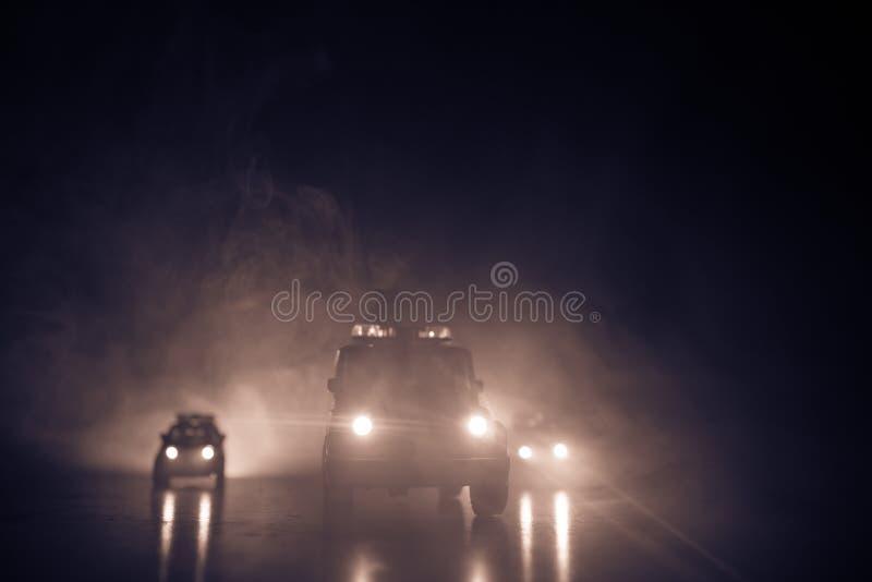 Carro de polícia que persegue um carro na noite com fundo da névoa Carro de 911 polícias da resposta de emergencia que apressa-se fotos de stock royalty free