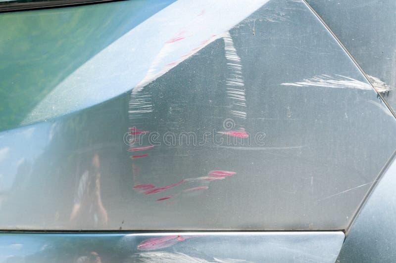 Carro de prata com pintura riscada com linhas vermelhas do outro veículo danificado no acidente do impacto ou no parque de estaci imagens de stock royalty free