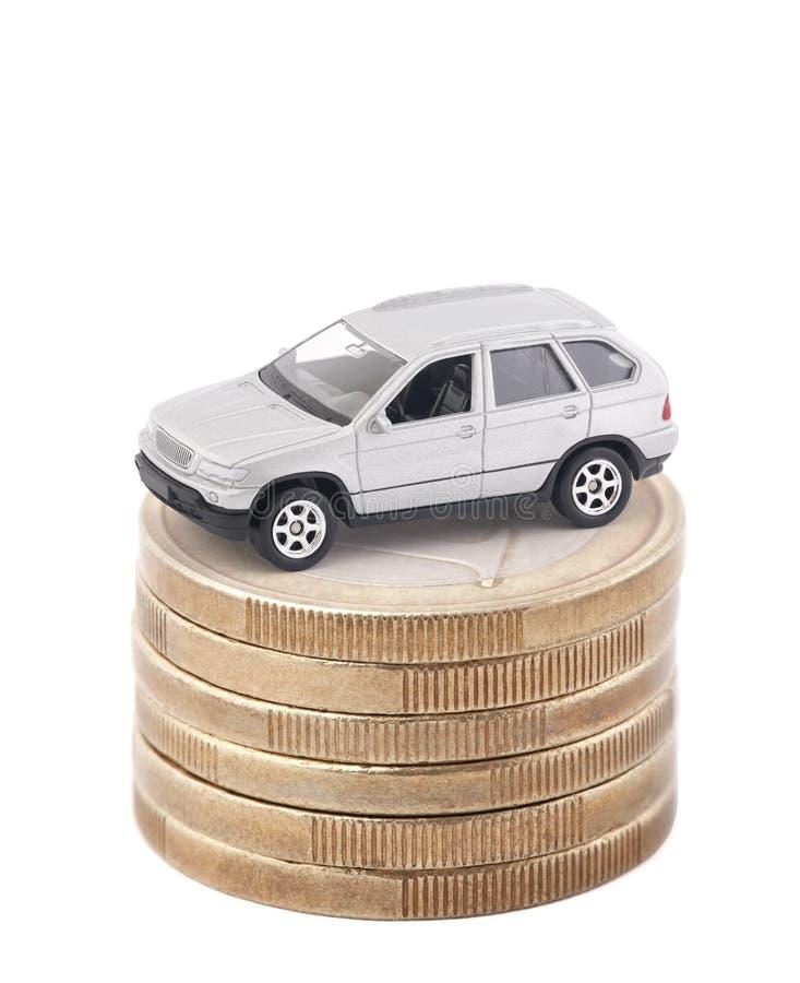 Carro de prata na pilha de euro- moedas isoladas no fundo branco imagens de stock