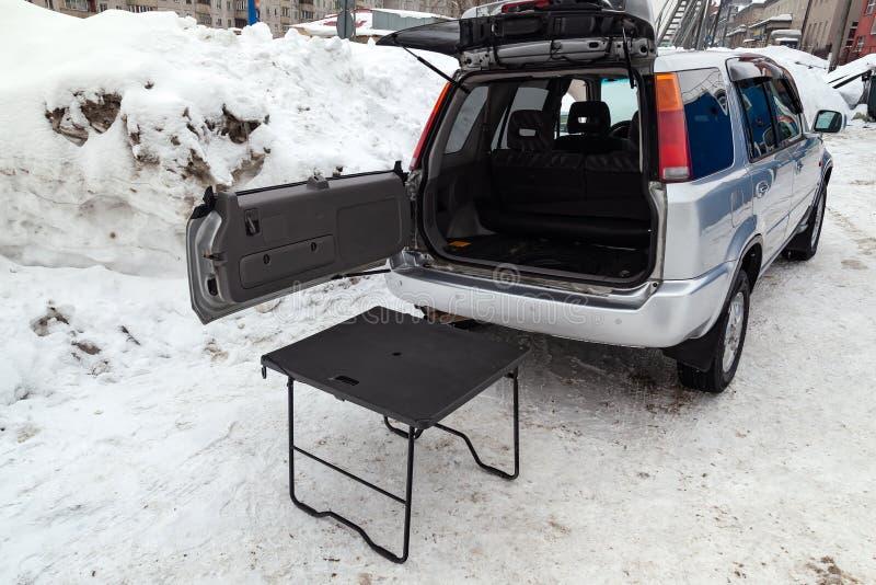 Carro de SUV na cor de prata com tronco e a tabela abertos para o piquenique perto dele após a limpeza antes da venda em um dia e fotos de stock royalty free