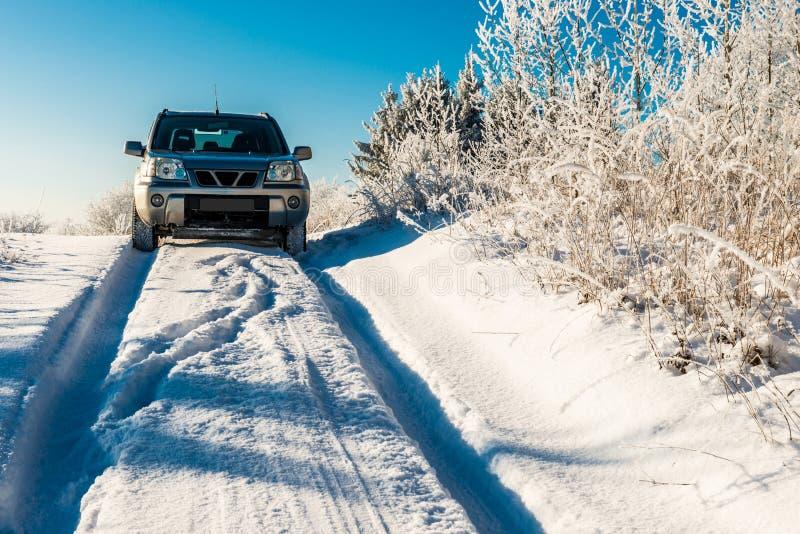 Carro de Suv que atravessa a estrada nevado do inverno foto de stock