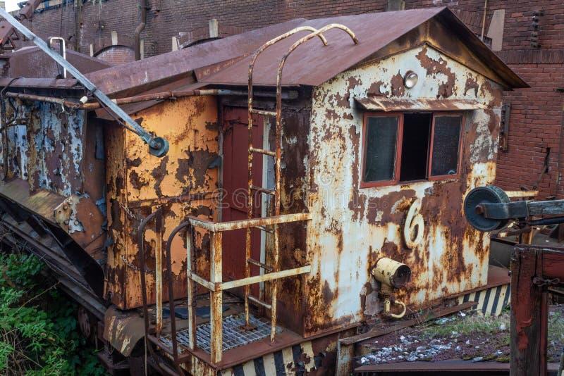 Carro de trem oxidado velho ao lado de uma construção industrial do tijolo fotografia de stock royalty free
