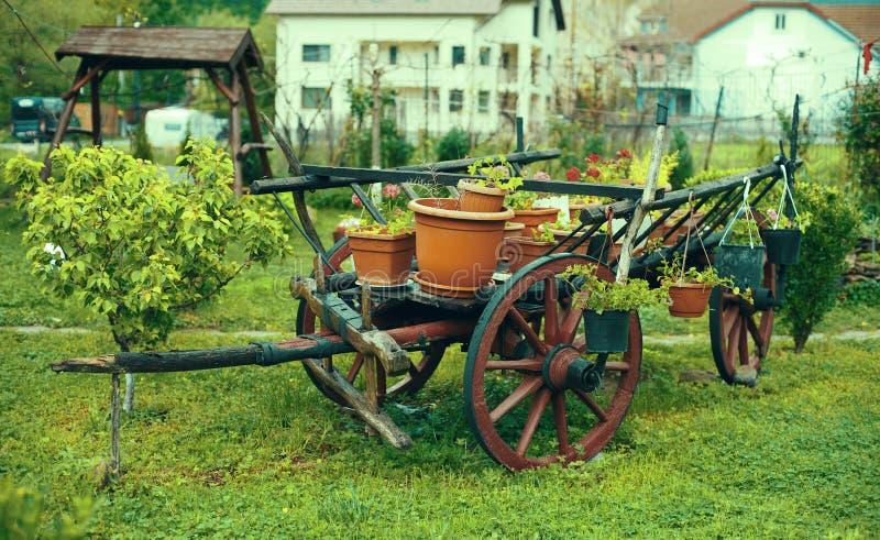 Carro decorativo com as flores na jarda imagens de stock royalty free