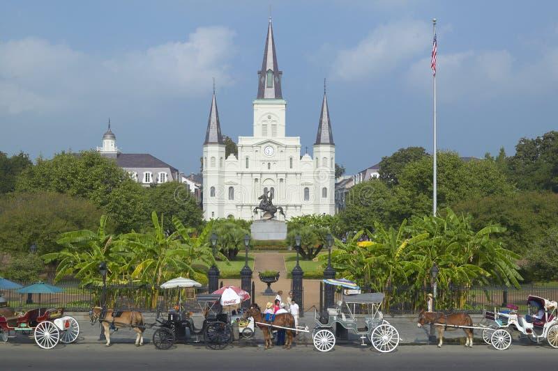 Carro del caballo y turistas delante de Andrew Jackson Statue y de St Louis Cathedral, Jackson Square en New Orleans, Luisiana imagenes de archivo