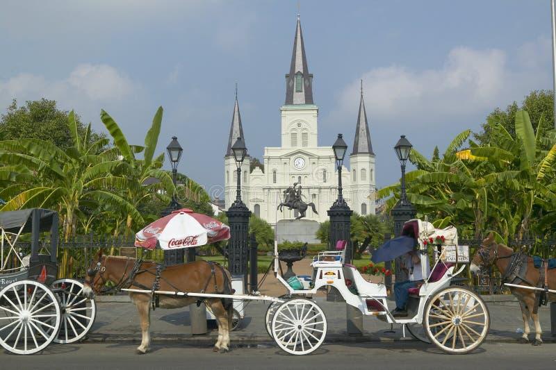 Carro del caballo y turistas delante de Andrew Jackson Statue y de St Louis Cathedral, Jackson Square en New Orleans, Luisiana fotos de archivo