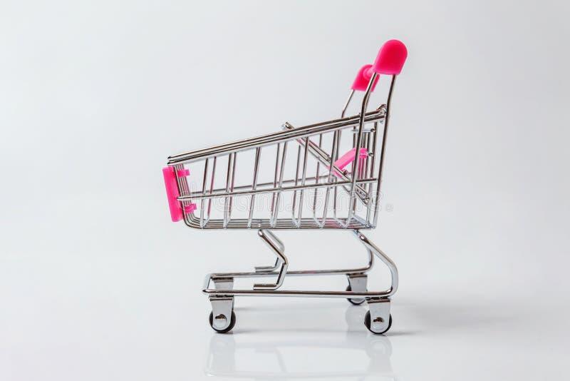 Carro del empuje del juguete del ultramarinos del pequeño supermercado en el fondo blanco foto de archivo