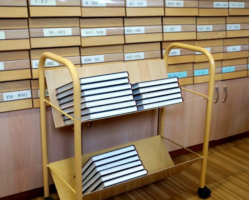 Carro del libro de la biblioteca con los libros en él con el catálogo de biblioteca en el fondo foto de archivo libre de regalías