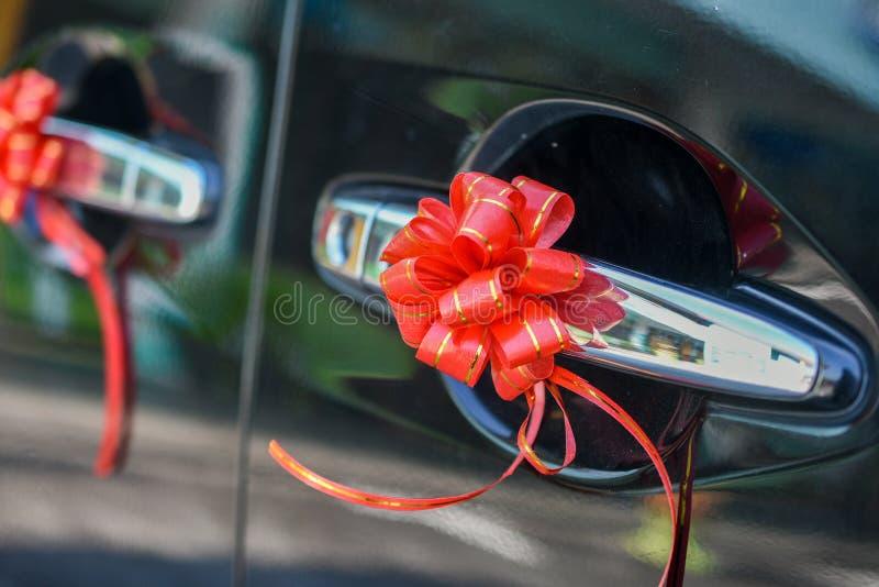 Carro do casamento da porta decorado com a flor vermelha da fita imagens de stock royalty free