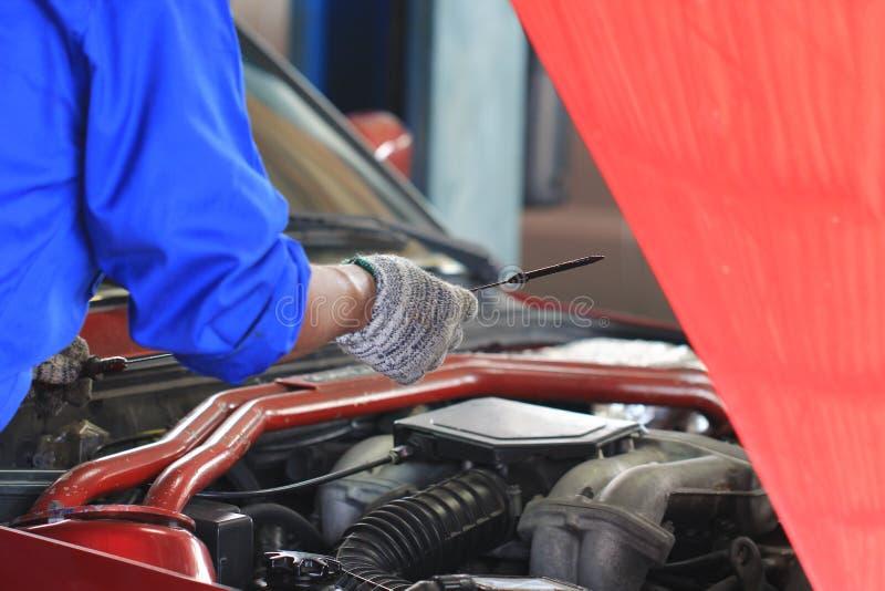 Carro do mecânico de carro ou óleo de exame da verificação no serviço de reparação de automóveis fotografia de stock royalty free