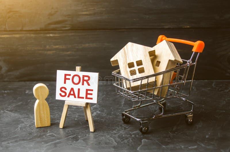 Carro do supermercado com casas e homem com um cartaz para a venda O conceito de vender uma casa, uns serviços dos bens imobiliár fotos de stock