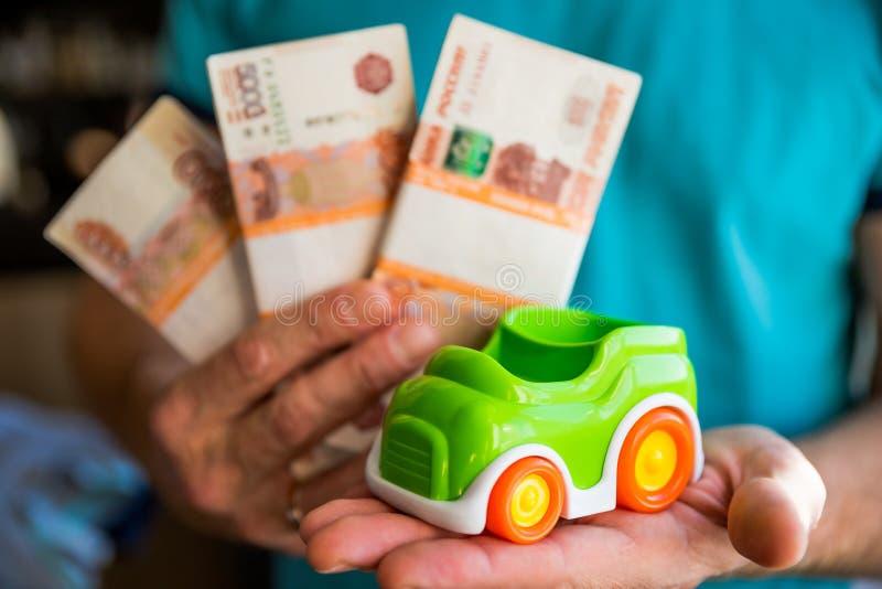 Carro e dinheiro nas mãos masculinas, conceito do empréstimo automóvel, dinheiro de salvamento para o conceito do carro, carro de fotos de stock