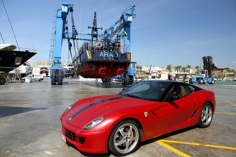 Carro e guarda costeira de Ferrari sobre um travelift na cidade de Alicante foto de stock