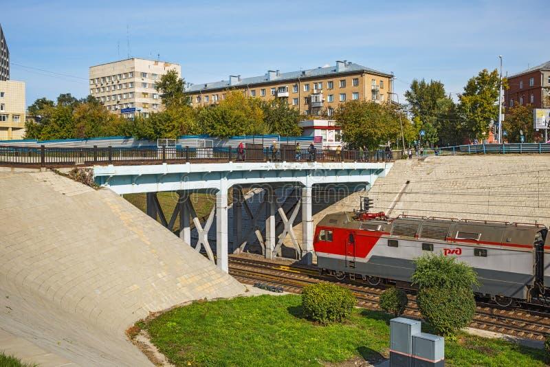 Carro e ponte pedestre sobre as trilhas de estrada de ferro no centro imagem de stock