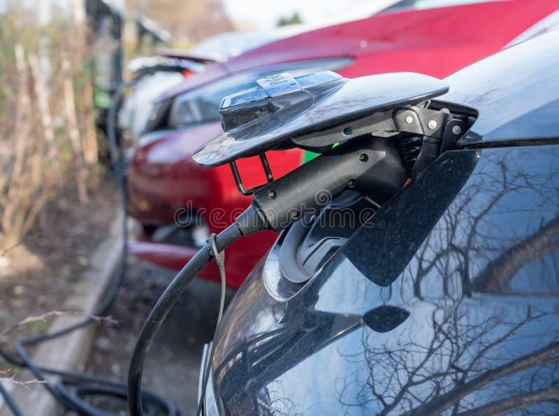 Carro elétrico de Nissan que está sendo recarregado no parque de estacionamento imagem de stock
