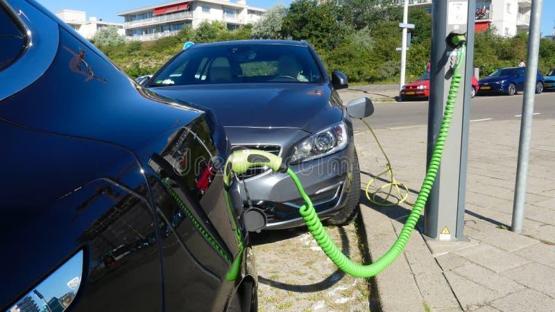 Carro elétrico de Tesla e baterias de carregamento híbridas de Volvo na estação responsável da tomada nos Países Baixos imagem de stock royalty free