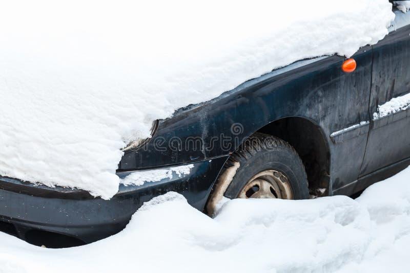 Carro estacionado velho coberto com a neve, fim acima imagens de stock