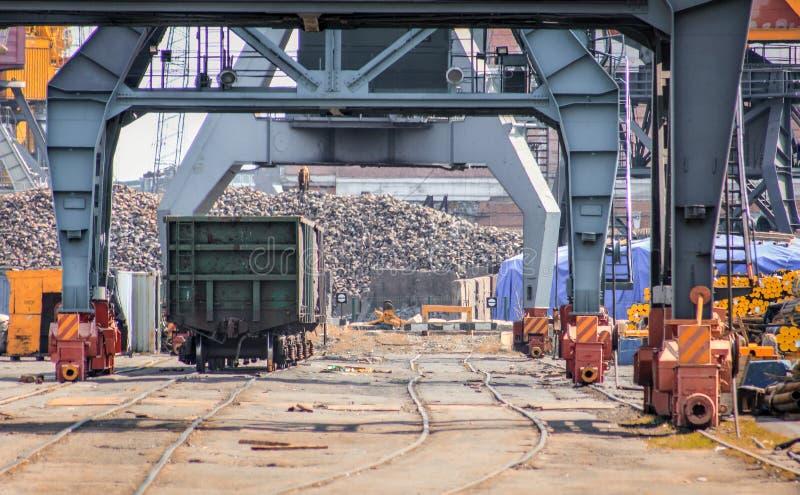 Carro ferroviario debajo de las gr?as cargadas en puerto mar?timo fotografía de archivo libre de regalías