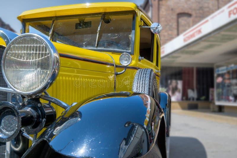 Carro histórico amarelo na opinião do close-up diagonalmente da parte dianteira, com pára-choques pretos, partes laterais com ent imagens de stock royalty free